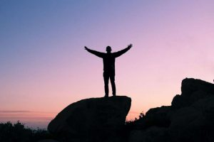 Silhouette of person standing on large rock with hands raised in victory