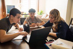 Mother homeschooling two children via laptop computer